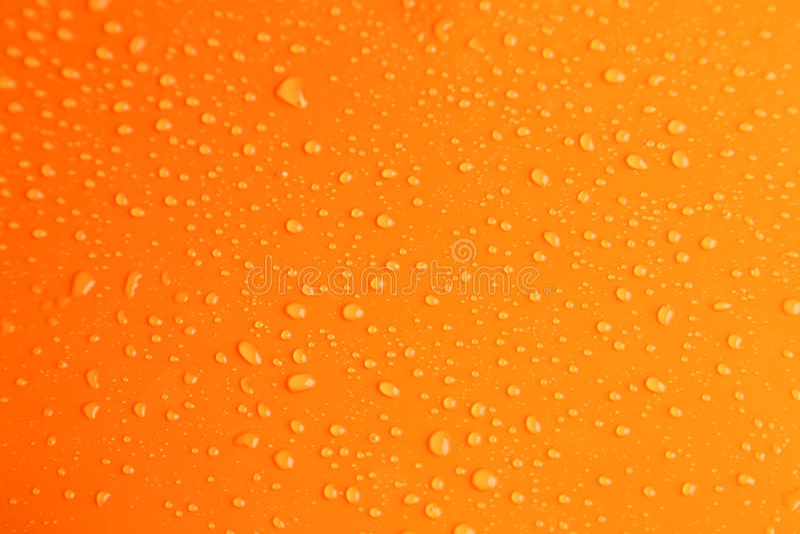 Οι πτώσεις νερού στο πορτοκαλί υπόβαθρο, κλείνουν επάνω στοκ εικόνα με δικαίωμα ελεύθερης χρήσης