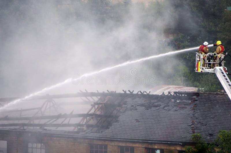 Οι πυροσβέστες σε μια ανυψωμένη πλατφόρμα που σβήνει την πυρκαγιά στον προηγούμενο clogs walkeys μύλο μέσα η γέφυρα στοκ εικόνες