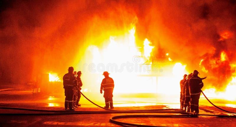 Οι πυροσβέστες στην αποθήκη συνδέουν την αντιμετώπιση της εκτυφλωτικής κόλασης στοκ φωτογραφία