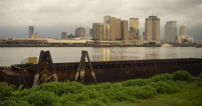 Οι ροές ποτάμι Μισισιπή με τις φορτηγίδες και τα κτήρια Νέα Ορλεάνη στοκ εικόνες
