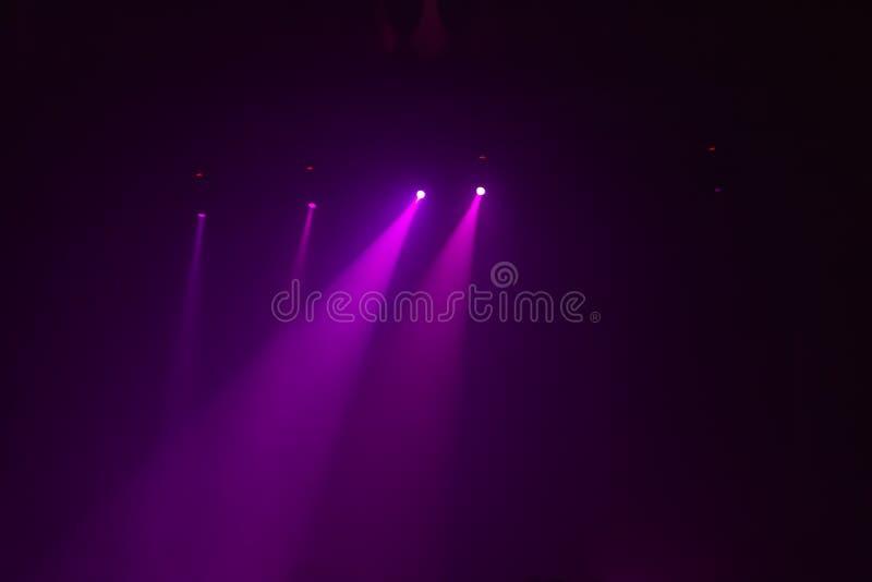 Οι ρόδινες ακτίνες μιας ομάδας από τα επίκεντρα σε ένα σκοτεινό υπόβαθρο σε μια συναυλία παρουσιάζουν στοκ εικόνα