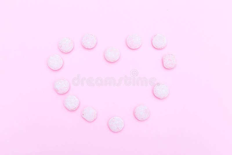 Οι ρόδινες καραμέλες είναι ευθυγραμμισμένες με μορφή μιας καρδιάς σε ένα ρόδινο backgro στοκ φωτογραφίες με δικαίωμα ελεύθερης χρήσης