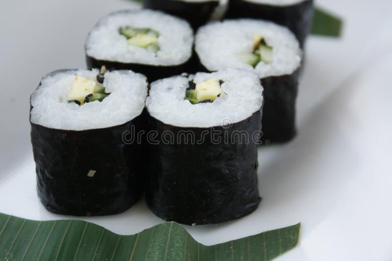 Οι ρόλοι των σουσιών με το nori ρυζιού και ψάρια σε ένα άσπρο πιάτο με chopsticks hashi στοκ φωτογραφία με δικαίωμα ελεύθερης χρήσης