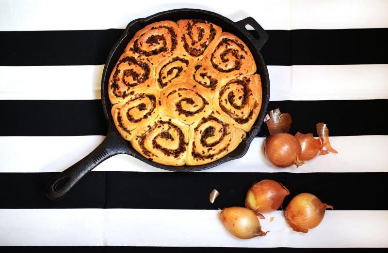 Οι ρόλοι ψωμιού με το κρεμμύδι, τα κουλούρια που ψήθηκαν χυτό στο σίδηρος τηγάνι στοκ φωτογραφία