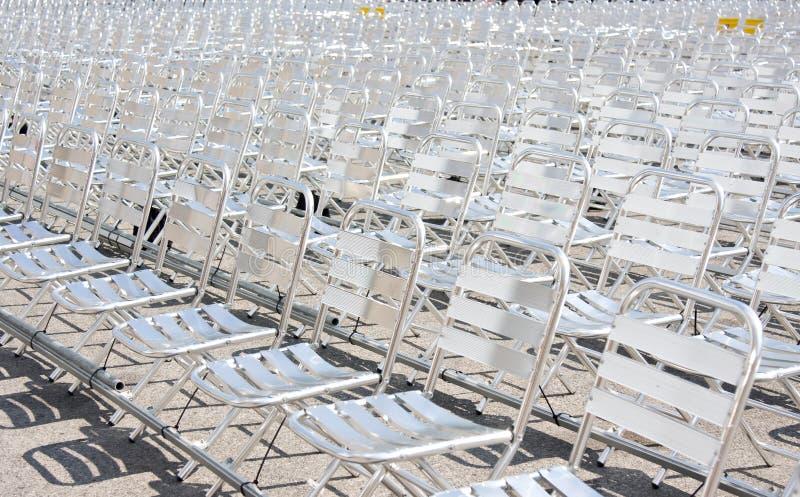 Οι σειρές του κενού μετάλλου προεδρεύουν των καθισμάτων που εγκαθίστανται για κάποια επιχειρησιακή γεγονός ή απόδοση στοκ φωτογραφία με δικαίωμα ελεύθερης χρήσης