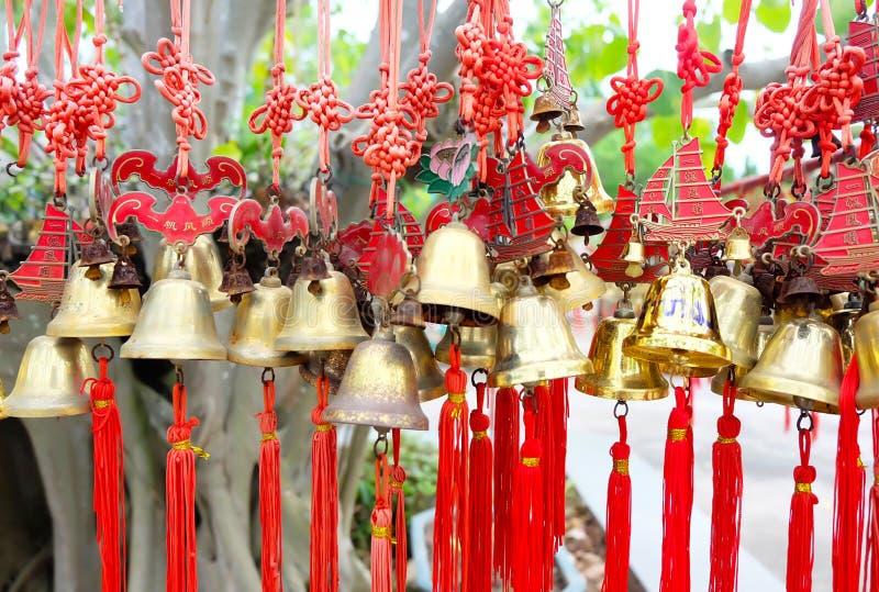 Οι σειρές του κόκκινου αέρα κουδουνιού ευημερίας κουδουνιών χρυσού βουδιστικού στους κινεζικούς λαούς ναών τους επιθυμούν και κρε στοκ εικόνες