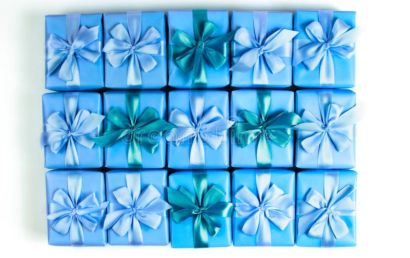 Οι σειρές των κιβωτίων με το σατέν κορδελλών διακοσμήσεων δώρων υποκύπτουν το μπλε Α που η τοπ άποψη του επιπέδου βρέθηκε στοκ εικόνα