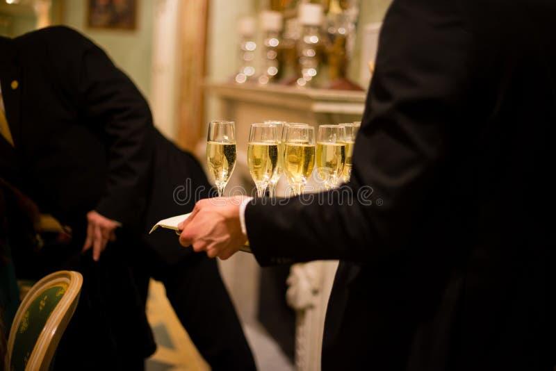 οι σερβιτόροι στη στολή εξυπηρετούν τα ποτήρια του λαμπιρίζοντας άσπρου κρασιού, στοκ φωτογραφίες με δικαίωμα ελεύθερης χρήσης