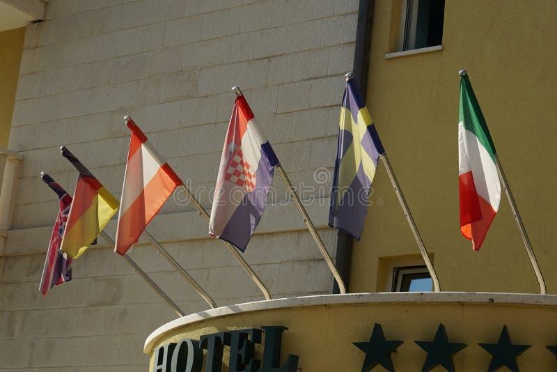 Οι σημαίες των διαφορετικών χωρών κρεμούν μπροστά από το ξενοδοχείο στοκ φωτογραφίες