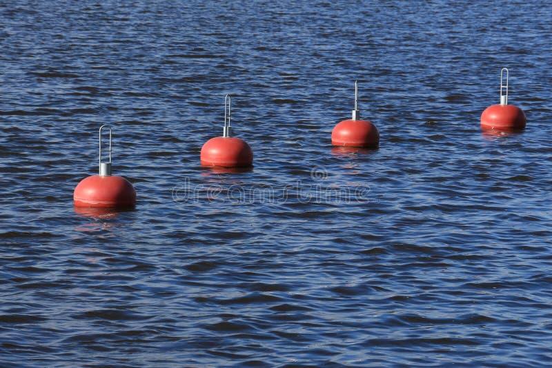 οι σημαντήρες κλείνουν το διαγώνιο κόκκινο επάνω στο ύδωρ στοκ φωτογραφία