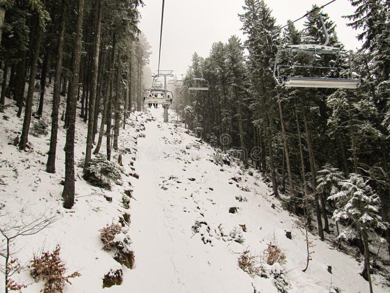 Οι σκιέρ αναρριχούνται επάνω στην κλίση με το τελεφερίκ στο χιονισμένο δάσος στοκ εικόνες