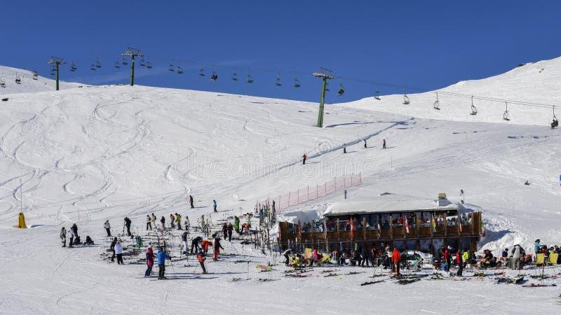 Οι σκιέρ και τα snowboarders με το εργαλείο τους χαλαρώνουν σε μια ξύλινη καμπίνα στο χιονοδρομικό κέντρο Λα Thuile Valle δ ` Aos στοκ εικόνες