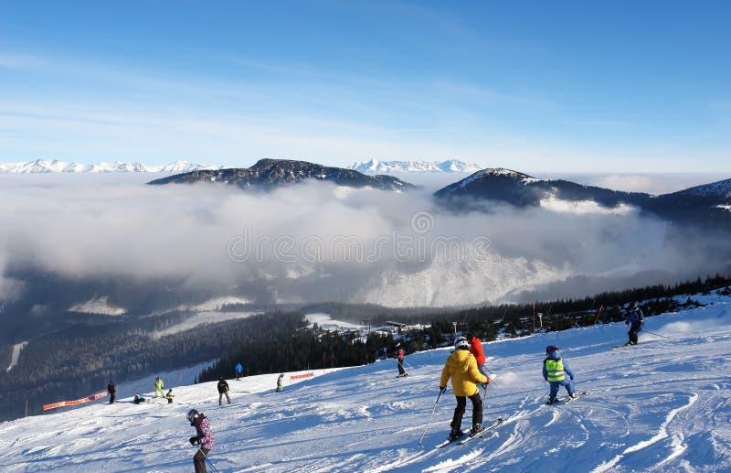 Οι σκιέρ στο σκι κλίνουν μια ηλιόλουστη ημέρα στο θέρετρο Jasna στοκ εικόνα