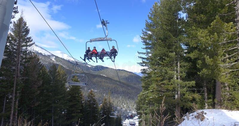 Οι σκιέρ, snowboarders που οδηγούν σε έναν ανελκυστήρα, μεταφορά στις κλίσεις σκι βουνών προσφεύγουν στοκ φωτογραφίες