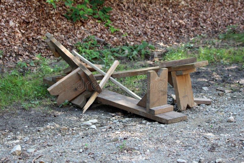 Οι σπασμένοι σπιτικοί ξύλινοι πάγκοι έφυγαν στο δρόμο αμμοχάλικου στο τοπικό δάσος μετά από τη μεγάλη θύελλα και τις πλημμύρες στοκ φωτογραφία με δικαίωμα ελεύθερης χρήσης