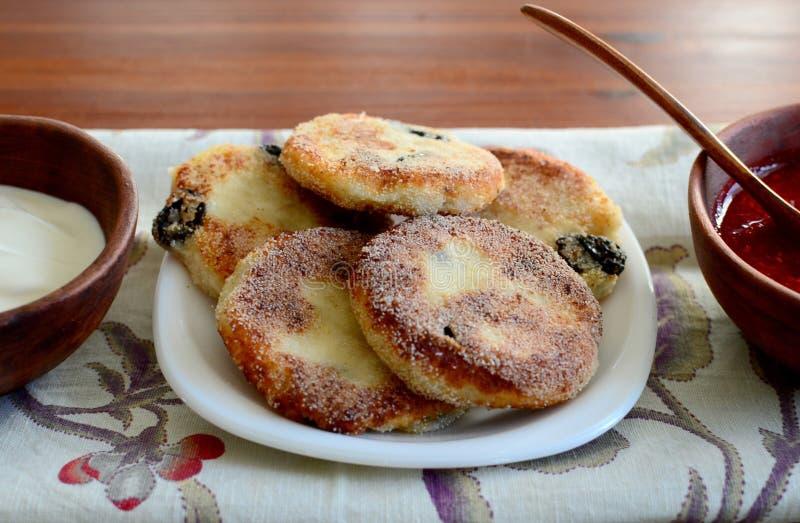 Οι σπιτικές τηγανίτες τυριών εξοχικών σπιτιών ξινίζουν τη μαρμελάδα σμέουρων κρέμας στο φλυτζάνι αργίλου στην πετσέτα λινού στοκ φωτογραφίες
