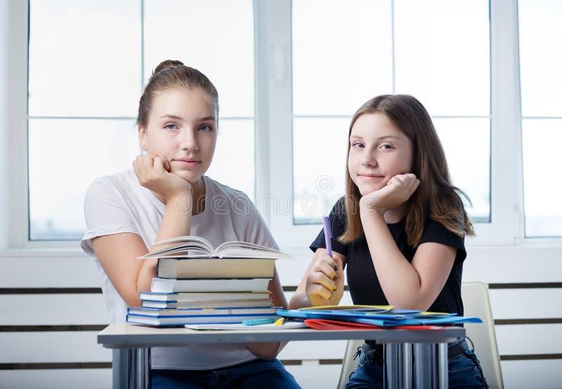Οι σπουδαστές εφήβων teens κάθονται στον πίνακα με τα βιβλία ST στοκ φωτογραφία με δικαίωμα ελεύθερης χρήσης