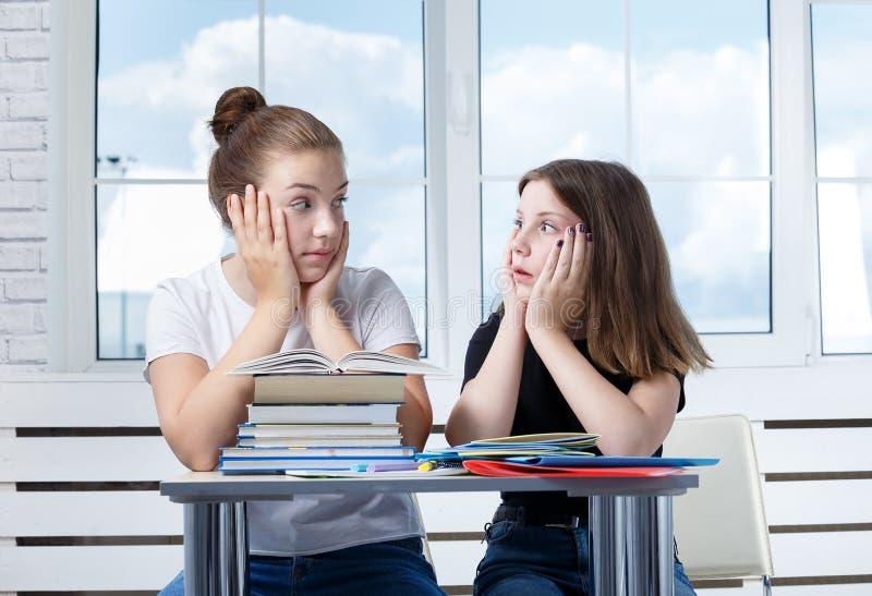 Οι σπουδαστές εφήβων teens κάθονται στον πίνακα με τα βιβλία ST στοκ φωτογραφία