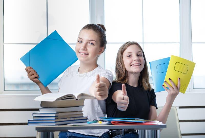 Οι σπουδαστές εφήβων teens κάθονται στον πίνακα με τα βιβλία ST στοκ εικόνες