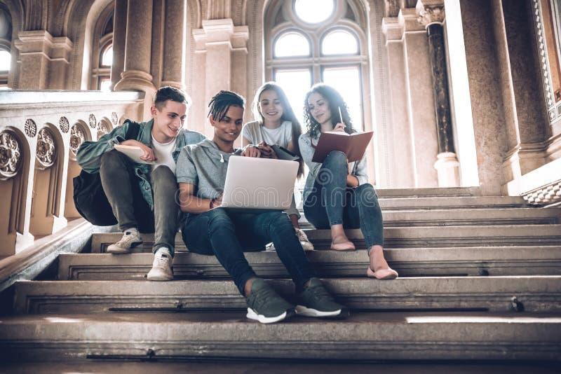 Οι σπουδαστές ξοδεύουν το χρόνο από κοινού Ομάδα Multiethnic νέων που εξετάζουν ένα lap-top και και που κάθονται στα βήματα στο π στοκ εικόνα με δικαίωμα ελεύθερης χρήσης