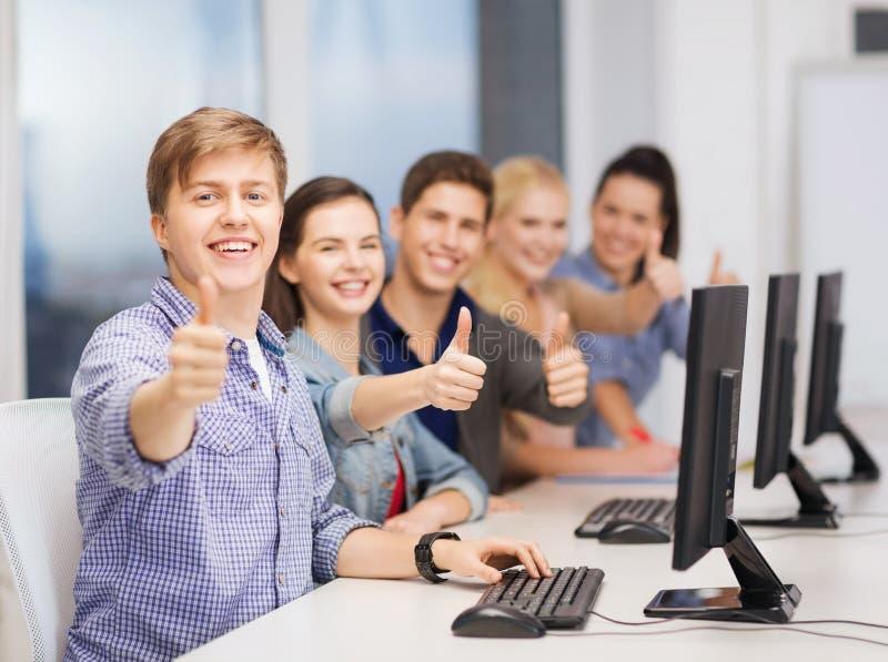 Οι σπουδαστές με τον υπολογιστή ελέγχουν να παρουσιάσουν αντίχειρες στοκ εικόνες