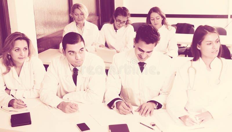 Οι σπουδαστές στα άσπρα παλτά ακούνε για να μιλήσουν στοκ εικόνα με δικαίωμα ελεύθερης χρήσης