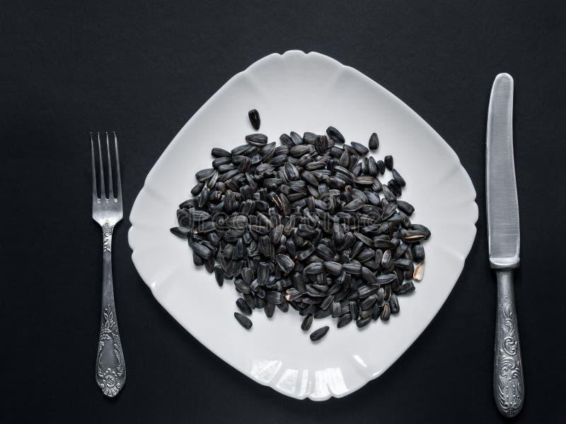 Οι σπόροι ηλίανθων βρίσκονται σε ένα άσπρο πιάτο σε ένα μαύρο υπόβαθρο στοκ εικόνες
