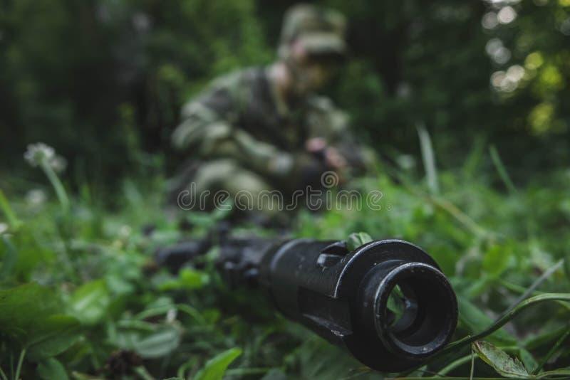 Οι στρατιωτικοί κάθονται στη χλόη και εξετάζουν το πυροβόλο όπλο του στοκ φωτογραφίες με δικαίωμα ελεύθερης χρήσης