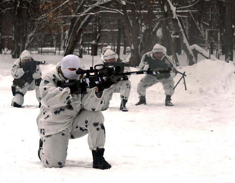 Οι στρατιώτες της ειδικής αποσύνδεσης επιλύουν το συντονισμό αγώνα στην ουδετεροποίηση των τρομοκρατών στο χειμερινό όρο στοκ φωτογραφία