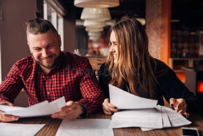 Οι συνάδελφοι συζητούν τα έγγραφα καθμένος σε έναν καφέ στοκ φωτογραφίες με δικαίωμα ελεύθερης χρήσης