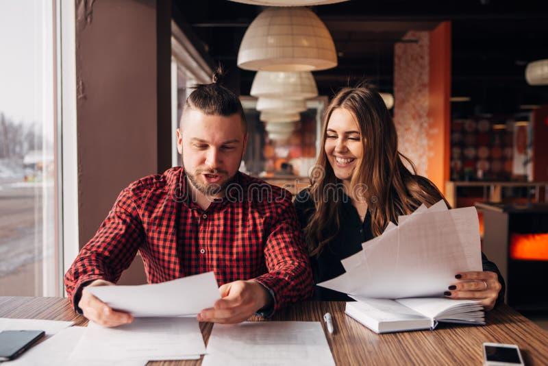 Οι συνάδελφοι συζητούν τα έγγραφα καθμένος σε έναν καφέ στοκ εικόνες