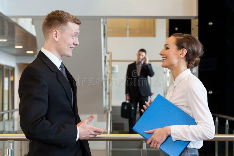 Οι συνάδελφοι που γελούν στην επιχείρηση κεντροθετούν την αίθουσα στοκ εικόνα