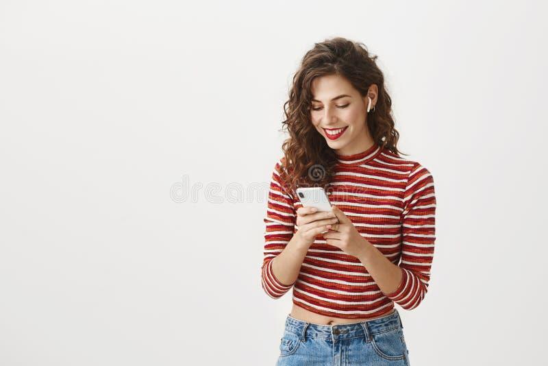 Οι συσκευές είναι μελλοντικές Πορτρέτο της συγκινημένης ευτυχούς Ευρωπαίας γυναίκας με το σγουρό hairstyle και την κόκκινη φθορά  στοκ φωτογραφία