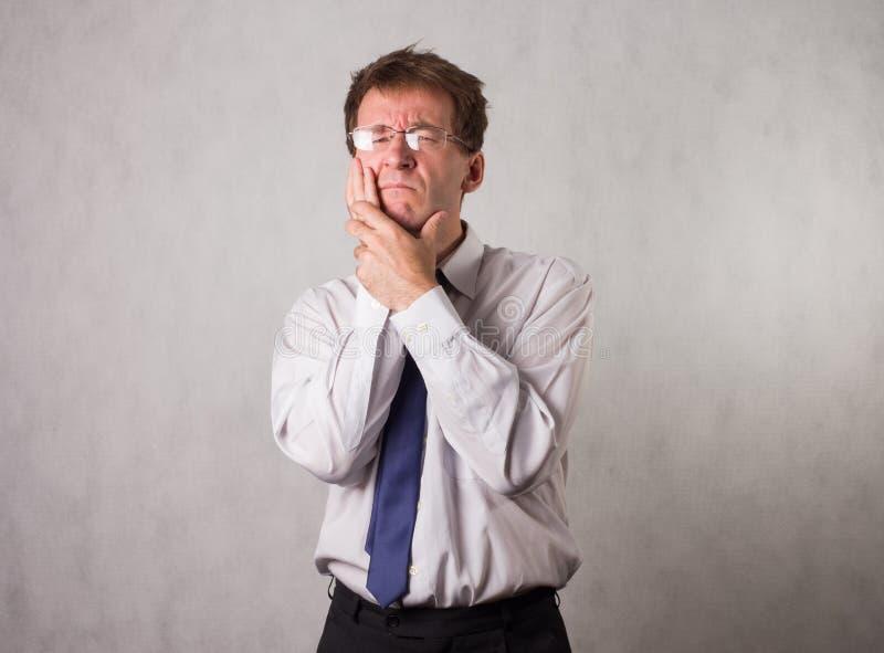 Οι συσπάσεις ατόμων στον πόνο και προσκολλώνται στο μάγουλό του Ανησυχεί για ένα κακό δόντι στοκ φωτογραφίες