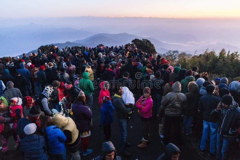 Οι συσσωρευμένοι άνθρωποι περιμένουν το πρώτο φως στην αυγή της νέας ημέρας έτους ` s με το βουνό και την ομίχλη στο υπόβαθρο στο στοκ εικόνα με δικαίωμα ελεύθερης χρήσης