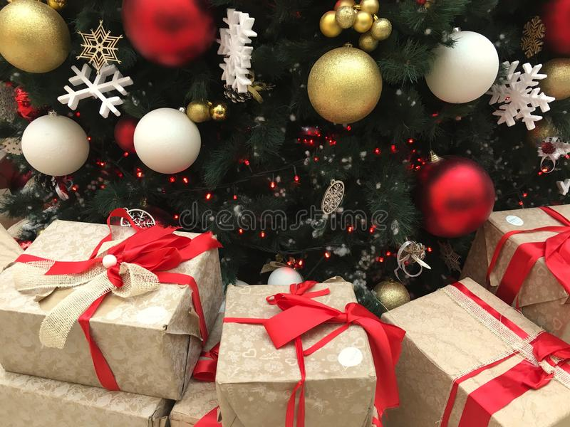 Οι σφαίρες Χριστουγέννων κάτω από το χριστουγεννιάτικο δέντρο με τα κιβώτια του νέου έτους είναι υπόβαθρο χειμερινών διακοπών δώρ στοκ εικόνες