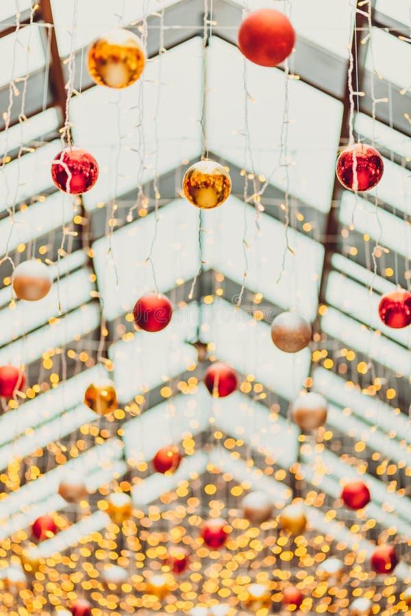 Οι σφαίρες Χριστουγέννων στο εκλεκτής ποιότητας φως νύχτας πόλεων bokeh και το φως Χριστουγέννων θόλωσαν το υπόβαθρο στη ημέρα τω στοκ εικόνα