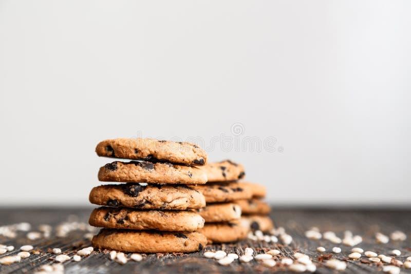 Οι σωροί των μπισκότων τσιπ σοκολάτας στο σκοτεινό πίνακα με το αντίγραφο χωρίζουν κατά διαστήματα στην κορυφή στοκ φωτογραφίες