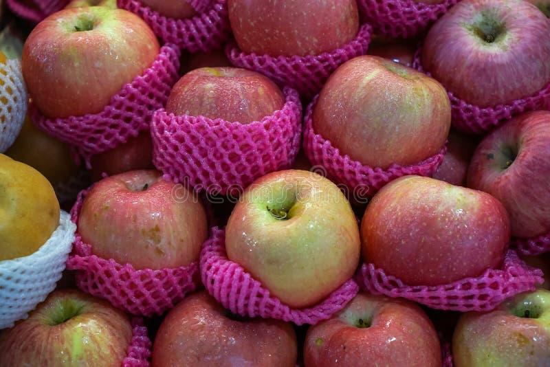 Οι σωροί των φρέσκων άφθονων όμορφων εύγευστων φρούτων μήλων κλίσης κόκκινων στο ρόδινο αφρό τυλίγουν την πώληση στην τοπική αγορ στοκ εικόνα