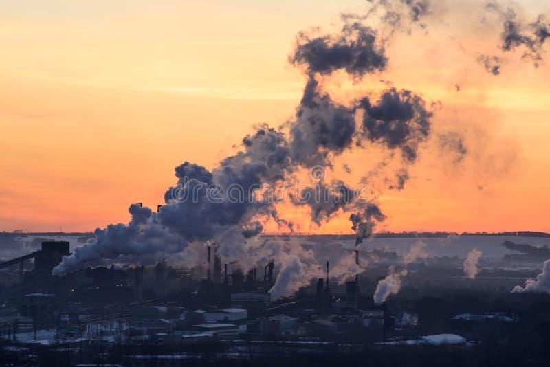 Οι σωλήνες των εγκαταστάσεων ρίχνουν έξω τον τοξικό καπνό στο ηλιοβασίλεμα στοκ φωτογραφία με δικαίωμα ελεύθερης χρήσης
