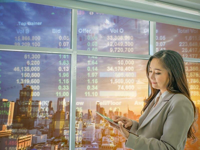 Οι σύγχρονες επιχειρησιακές γυναίκες εξετάζουν το πράγμα ταμπλετών για το χρηματιστήριο, CI στοκ εικόνες