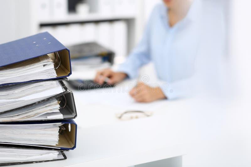 Οι σύνδεσμοι με τα έγγραφα περιμένουν να υποβληθούν σε επεξεργασία από την επιχειρησιακό γυναίκα ή το λογιστή πίσω στη θαμπάδα Εσ στοκ εικόνα