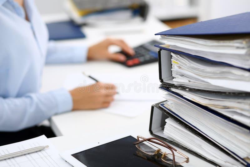 Οι σύνδεσμοι με τα έγγραφα περιμένουν να υποβληθούν σε επεξεργασία από την επιχειρησιακό γυναίκα ή το λογιστή πίσω στη θαμπάδα Εσ στοκ φωτογραφίες