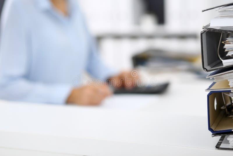 Οι σύνδεσμοι με τα έγγραφα περιμένουν να υποβληθούν σε επεξεργασία από την επιχειρησιακό γυναίκα ή το λογιστή πίσω στη θαμπάδα Εσ στοκ εικόνες