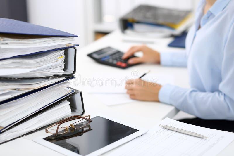 Οι σύνδεσμοι με τα έγγραφα περιμένουν να υποβληθούν σε επεξεργασία από την επιχειρησιακό γυναίκα ή το λογιστή πίσω στη θαμπάδα Εσ στοκ φωτογραφίες με δικαίωμα ελεύθερης χρήσης