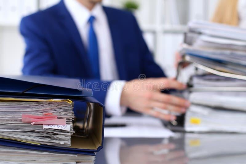 Οι σύνδεσμοι με τα έγγραφα περιμένουν να υποβληθούν σε επεξεργασία με τον επιχειρηματία και το γραμματέα πίσω στη θαμπάδα Λογιστι στοκ εικόνες με δικαίωμα ελεύθερης χρήσης