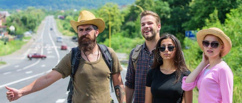 Οι ταξιδιώτες προσπαθούν να σταματήσουν το αυτοκίνητο Hitchhikers φίλων που ταξιδεύουν τη θερινή ηλιόλουστη ημέρα Αρχίστε τη μεγά στοκ φωτογραφία με δικαίωμα ελεύθερης χρήσης