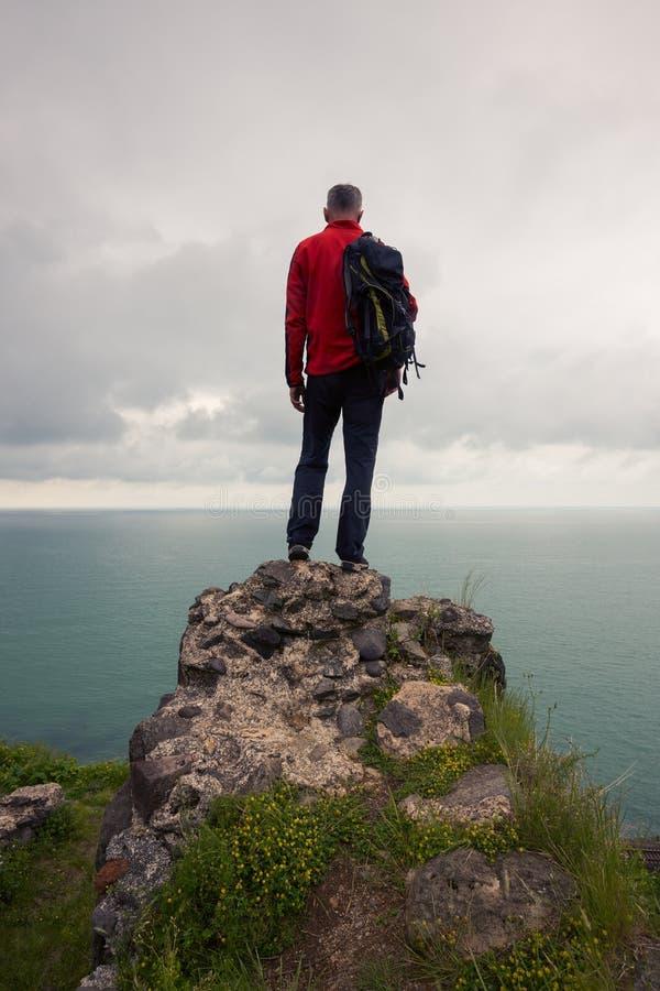 Οι ταξιδιωτικές στάσεις σε έναν απότομο βράχο και εξετάζουν τη θάλασσα στοκ φωτογραφίες με δικαίωμα ελεύθερης χρήσης
