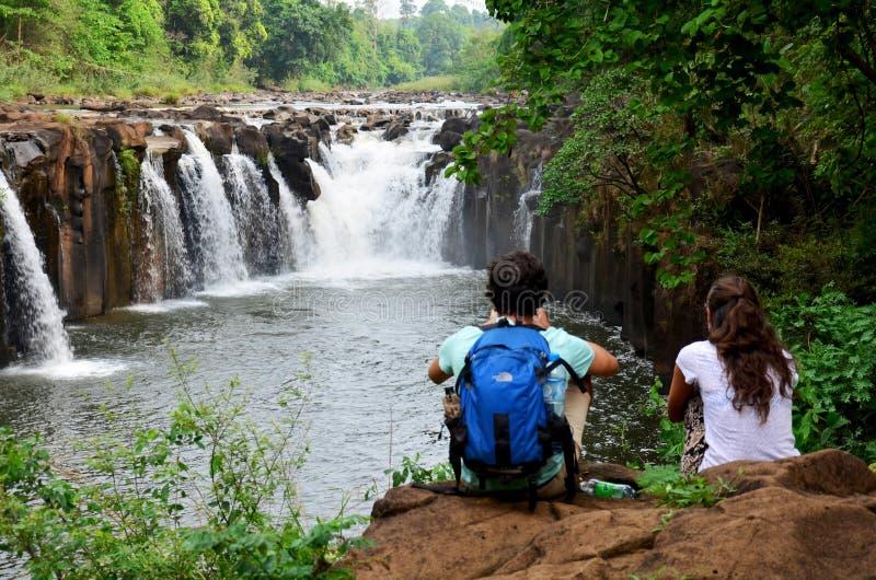 Οι ταξιδιωτικοί εραστές αλλοδαπών που κάθονται και χαλαρώνουν στην πέτρα στοκ φωτογραφία με δικαίωμα ελεύθερης χρήσης