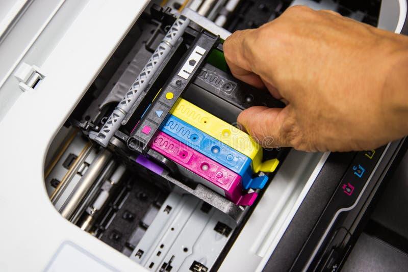 Οι τεχνικοί εγκαθιστούν την κασέτα Inkjet εκτυπωτών χρώματος στοκ φωτογραφία